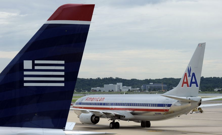 An American Airlines jetliner and a US Airways plane are pictured on the apron at Ronald Reagan Washington National Airport in Arlington, Va., on Tuesday, Aug. 13, 2013. (AP Photo/Susan Walsh)