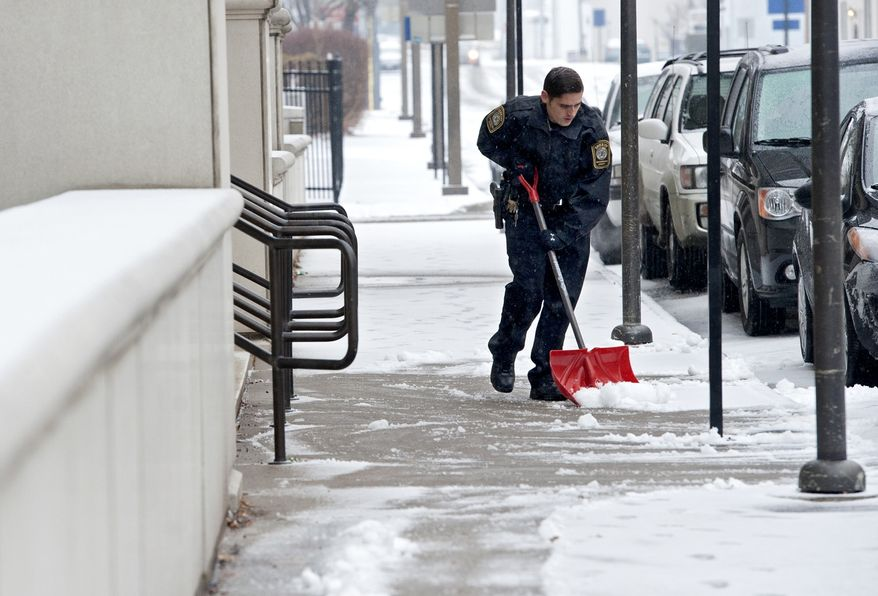 Corporal Cory Madison with the Rockingham County Sheriffs Department, shovels off snow and ice from in front of the Rockingham-Harrisonburg Judicial Center on Sunday, Dec. 8, 2013 in Harrisonburg, Va.  More than 89,000 customers in Virginia are without electricity as a winter storm moves across the state.  (AP Photo/Daily News-Record, Jason Lenhart)