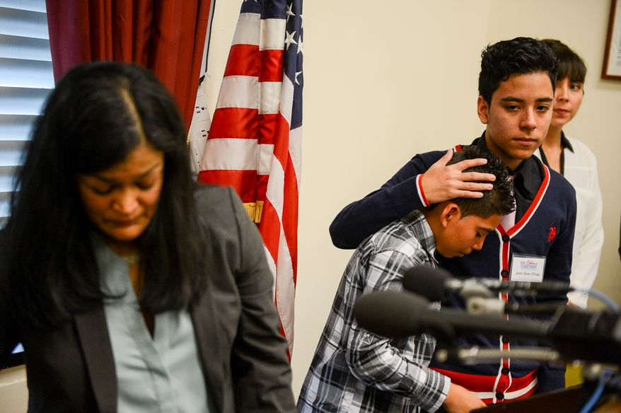 Charlie Hoz second from left, of Homestead, Fla., who's father was deported to Mexico this year and whose mother is also undocumented, is comforted by Javier Omar Ortega, 16, of Oakland, Calif., second from right, who's mother was separated from him 3 years ago, as they two speak out with other children of deportees to call on congress to pass immigration reform at a press conference on Capitol Hill, Washington, D.C., Monday, December 9, 2013. (Andrew Harnik/The Washington Times)
