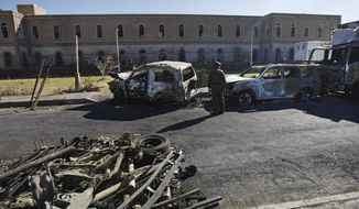 ** FILE ** A Yemeni soldier looks at damaged vehicles at the scene where a suicide car bomber and heavily armed gunmen, killed scores and wounded more than a hundred in a fierce battle in the heart of Yemen's capital of Sanaa Thursday, Dec. 5, 2013, at the Defense Ministry complex in Sanaa, Yemen. (AP Photo/Hani Mohammed)