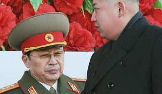 ** FILE ** In this Feb. 16, 2012, photo, North Korean leader Kim Jong-un walks past his uncle Jang Song Thaek, left, after reviewing a parade of thousands of soldiers and commemorating the 70th birthday of the late Kim Jong-il in Pyongyang, North Korea. North Korea announced Monday, Dec. 9, 2013 it had sacked leader Jang, long considered the country's No. 2 power. (AP Photo/Kyodo News)