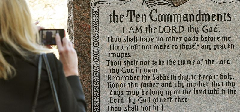 """** FILE ** On Nov. 15, 2012, a woman photographs a granite monument engraved with the Ten Commandments after it was erected on the north side of the Capitol in Oklahoma City. The word """"Sabbath"""" was misspelled on the monument. (AP Photo/The Oklahoman, Jim Beckel)"""