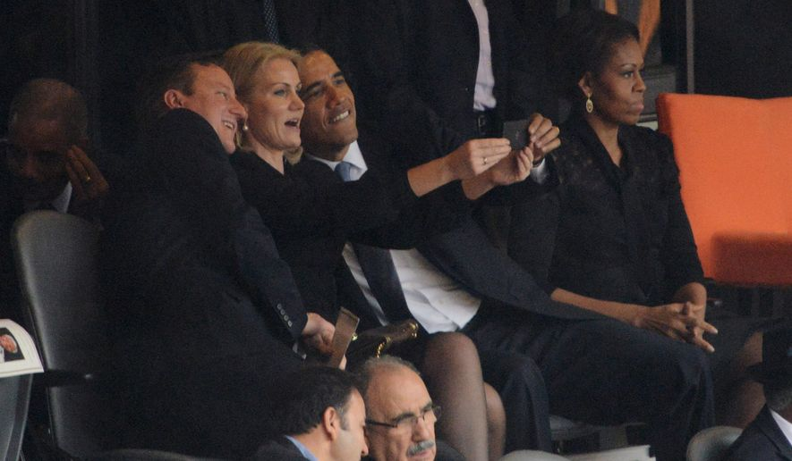 Selfie: President Obama gets some assistance from Danish Prime Minister Helle Thorning-Schmidt holding a smartphone to pose for a picture with British Prime Minister David Cameron. First lady Michelle Obama clearly stayed away from the antics. (Agence France-Presse/Getty Images)