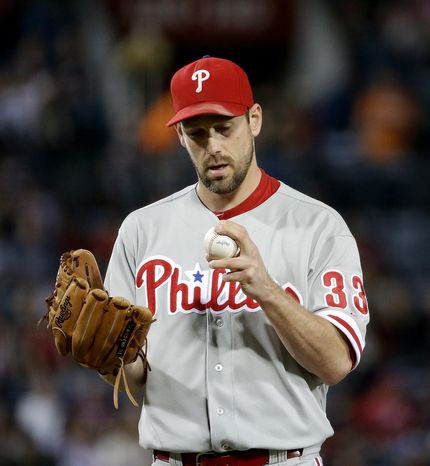 Philadelphia Phillies starting pitcher Cliff Lee looks at the ball before throwing in the first inning of a baseball game against the Atlanta Braves, Friday, Sept. 27, 2013, in Atlanta. (AP Photo/David Goldman)