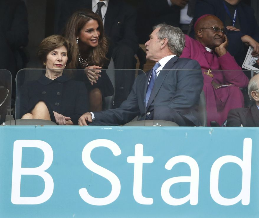 CORRECTS ID OF PERSON AT CENTER   Jordan's Queen Rania, center, speaks with Former U.S. President George W. Bush and his wife Laura during the memorial service for former South African president Nelson Mandela at the FNB Stadium in Soweto near Johannesburg, Tuesday, Dec. 10, 2013. Right is Retired Anglican Archbishop Desmond Tutu. (AP Photo/Matt Dunham)