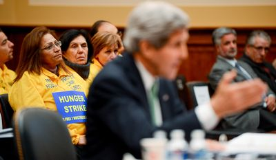 Members of the audience wear signs calling for a hunger strike over seven Iranian dissidents taken hostage by Iraqi Special Forces from Camp Ashraf as U.S. Secretary of State John Kerry appears before the House Foreign Affairs Committee to testify about the Iran Nuclear Deal at a hearing on Capitol Hill, Washington, D.C., Tuesday, December 10, 2013. (Andrew Harnik/The Washington Times)