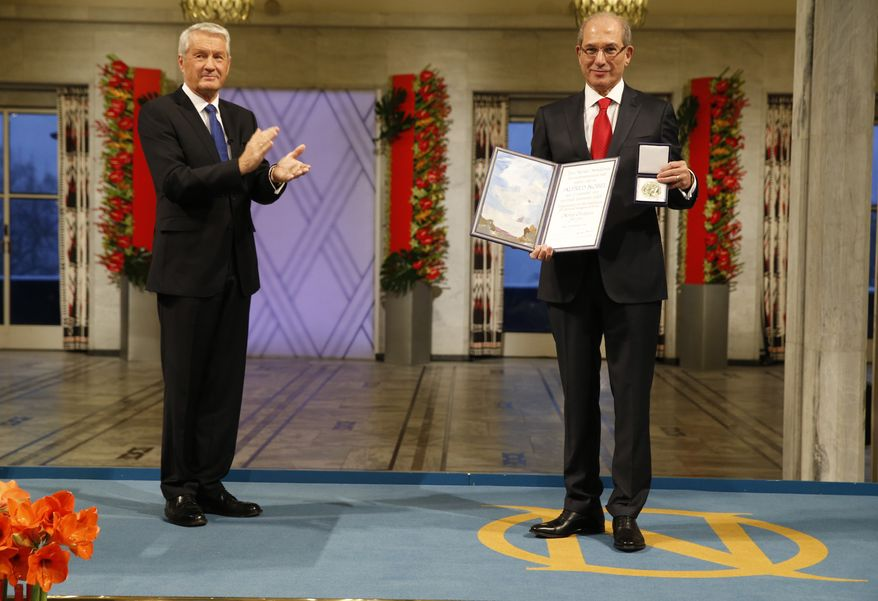 Ahmet Uzumcu (right), director-general of the Organization for the Prohibition of Chemical Weapons, accepts the Nobel Peace Prize on behalf of his organization from Thorbjorn Jagland, chairman of the Norwegian Nobel Committee, at City Hall in Oslo on Tuesday, Dec. 10, 2013. (AP Photo/Cornelius Poppe/NTB scanpix)