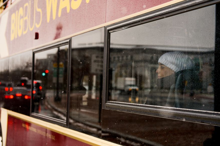 A woman looks out at Union Station from a tourism bus as morning snow falls, closing the Federal Government and area schools, Washington, D.C., Tuesday, December 10, 2013. (Andrew Harnik/The Washington Times)