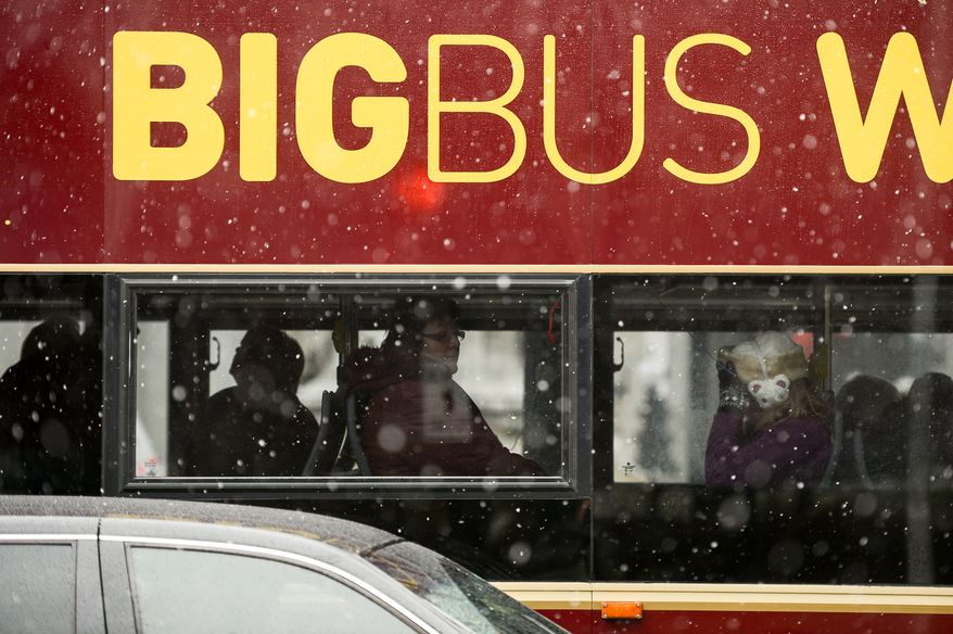 Riders make their way past Union Station on a tourism bus as morning snow falls, closing the Federal Government and area schools, Washington, D.C., Tuesday, December 10, 2013. (Andrew Harnik/The Washington Times)
