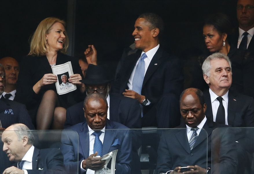 President Barack Obama jokes with Danish prime minister, Helle Thorning-Schmidt, left, as first lady Michelle Obama looks on at right during the memorial service for former South African president Nelson Mandela at the FNB Stadium in Soweto, near Johannesburg, South Africa, Tuesday Dec. 10, 2013. (AP Photo/Matt Dunham)