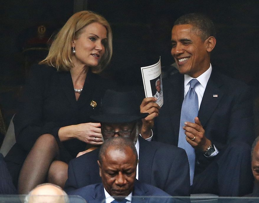 President Barack Obama laughs with Danish prime minister, Helle Thorning-Schmidt, during the memorial service for former South African president Nelson Mandela at the FNB Stadium in Soweto, near Johannesburg, South Africa, Tuesday Dec. 10, 2013. (AP Photo/Matt Dunham)