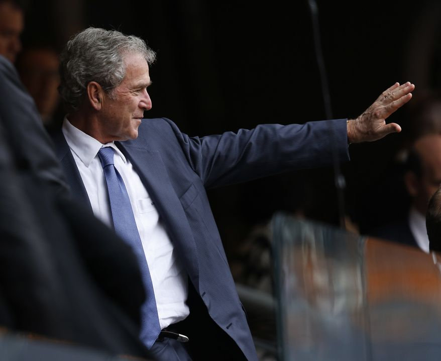 ** FILE ** Former U.S. President George W. Bush waves during the memorial service for former South African president Nelson Mandela at the FNB Stadium in Soweto near Johannesburg, Tuesday, Dec. 10, 2013. (AP Photo/Ben Curtis)