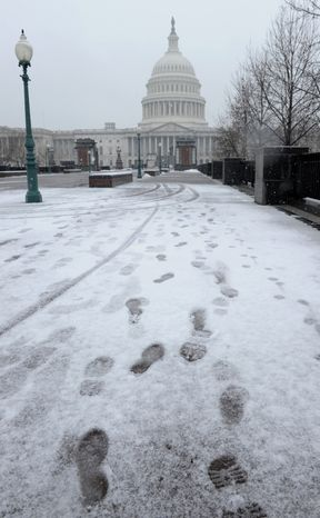 Footprints in the snow lead to the Capitol in Washington, Tuesday, Dec. 10, 2013. In Washington. Snow was falling at daybreak, but traffic problems failed to materialize as many workers stayed home. Non-emergency federal employees were granted an excused absence and others were told to telecommute, according to the U.S. Office of Personnel Management. (AP Photo/Susan Walsh)