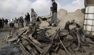 Afghan police examin the remains of a car after a suicide attack near a gate used by NATO troops, in Kabul, Afghanistan, Wednesday, Dec. 11, 2013. The Afghan Interior Ministry says a car bomb has exploded near a gate used by NATO troops in the northern section of the Kabul airport. There were no casualties in the attack. (AP Photo/Rahmat Gul)