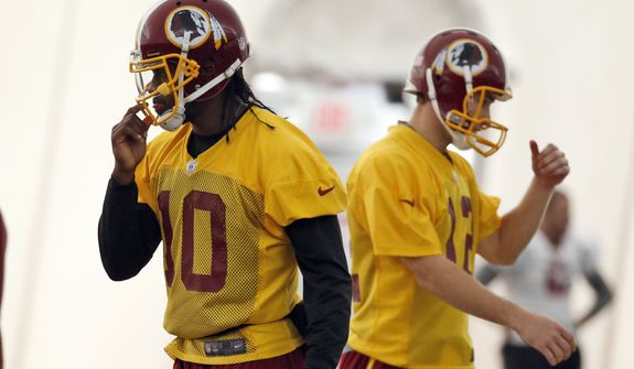 Washington Redskins quarterbacks Robert Griffin III, left, and Kirk Cousins, work during their NFL football practice Wednesday, Dec. 11, 2013, in Ashburn, Va. Cousins will start for the Redskins on Sunday, and Griffin III will be the No. 3 quarterback behind Rex Grossman. (AP Photo/Alex Brandon)