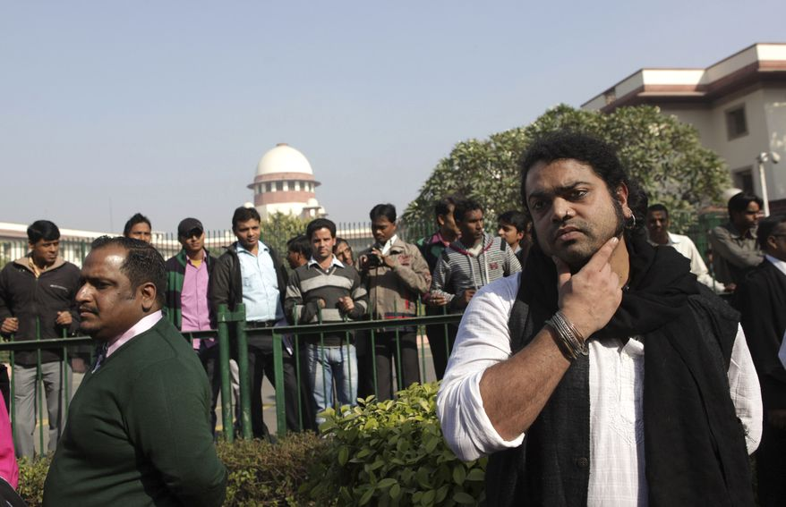 Indian gay rights activists and others stand outside the Supreme Court after the top court ruled that a colonial-era law criminalizing homosexuality will remain in effect in India in New Delhi, India, Wednesday, Dec. 11, 2013. (AP Photo/Tsering Topgyal)
