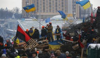 Pro-European Union activists wave flags celebrating riot police leaving form the Independence Square in Kiev, Ukraine, Wednesday, Dec. 11, 2013. Security forces clashed with protesters as they began tearing down opposition barricades and tents set up in the center of the Ukrainian capital early Wednesday, in an escalation of the weeks-long standoff threatening the leadership of President Viktor Yanukovych. (AP Photo/Sergei Grits)
