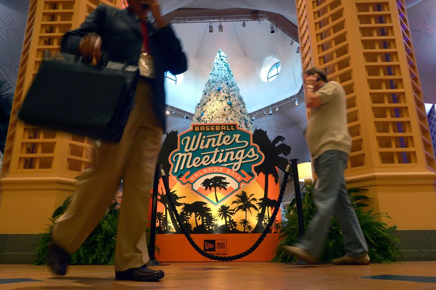 Guests walk past a sign welcoming attendees of baseball's winter meetings in Lake Buena Vista, Fla., Wednesday, Dec. 11, 2013.(AP Photo/Phelan M. Ebenhack)