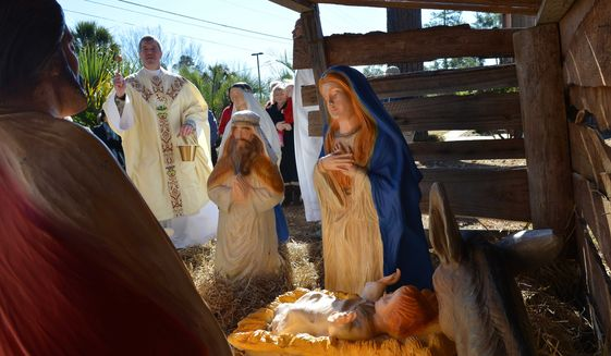 In this Dec. 12, 2013, photo released by the U.S. Air Force, Air Force Chaplain Lt. Col. Richard Fitzgerald, 20th Fighter Wing chaplain, sprinkles holy water over the Nativity scene at Shaw Air Force Base S.C. (AP Photo/U.S. Air Force, Senior Airman Ashley L. Gardner) ** FILE **