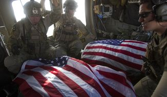 ** FILE ** In this Oct. 10, 2010, file photo, U.S. Air Force pararescuemen travel in a medevac helicopter with the American flag-draped bodies of U.S. soldiers who were killed in a roadside bomb attack in Afghanistan's Kandahar province. The Pararescuemen and pilots from the 46th and 26th Expeditionary Rescue Squadrons responded to the attack which killed two American soldiers and wounded three others. (AP Photo/David Guttenfelder, File)