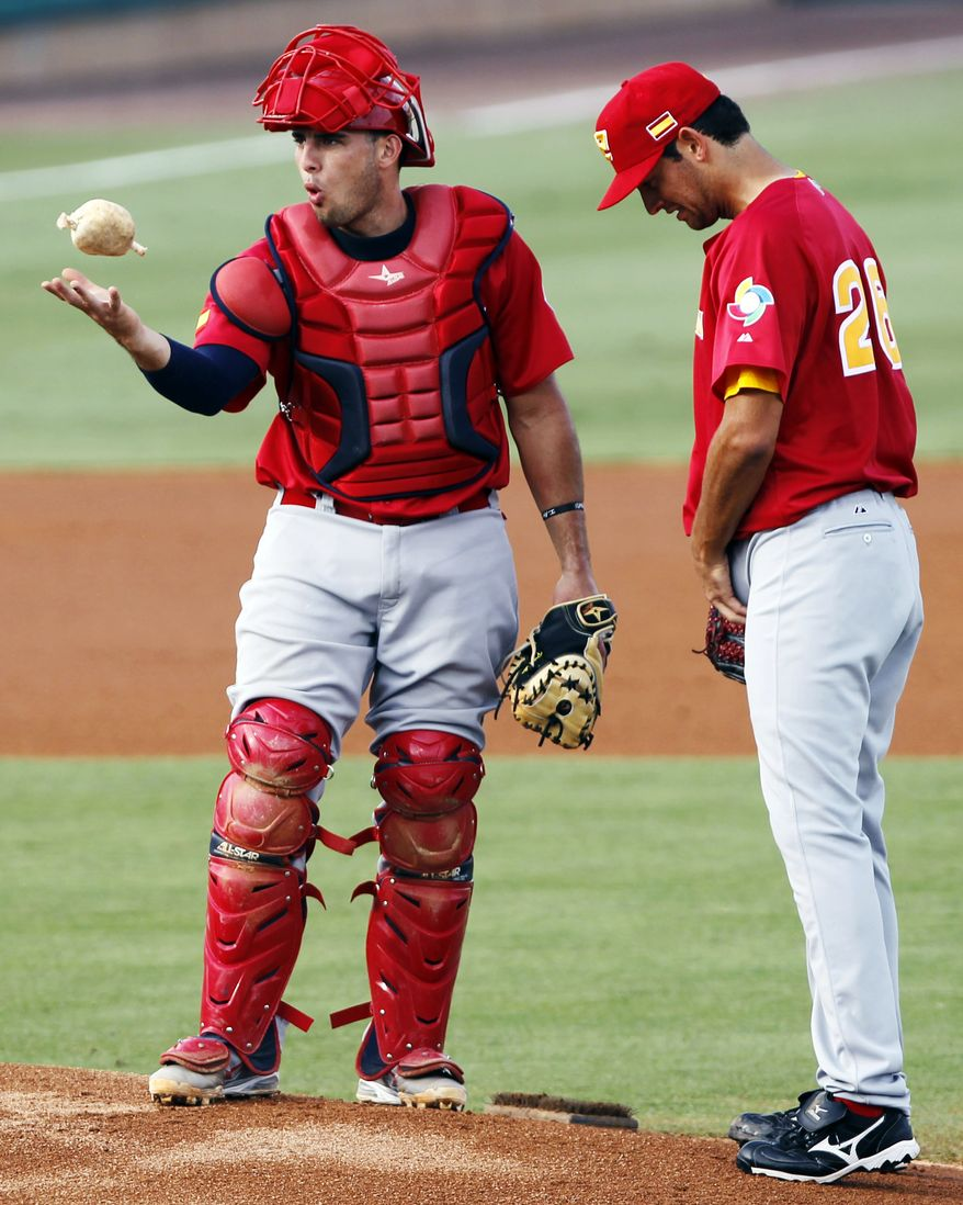 **FILE** Spain catcher Adrian Nieto, left, of the Washington Nationals, juggles with the resin bag as he talks to Eric Gonzalez in the first inning of a World Baseball Classic qualifier baseball game against Israel in Jupiter, Fla., Sunday, Sept. 23, 2012. (AP Photo/Alan Diaz)