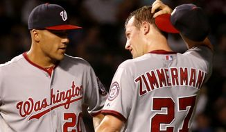 Washington Nationals starting pitcher Jordan Zimmermann (27) scratches his head as he talks with shortstop Ian Desmond during the fifth inning of a baseball game against the Chicago Cubs, Monday, Aug. 19, 2013, in Chicago. Shortly after the conversation Zimmermann gave up a three-run home run to the Cubs' Dioner Navarro. (AP Photo/Charles Rex Arbogast)