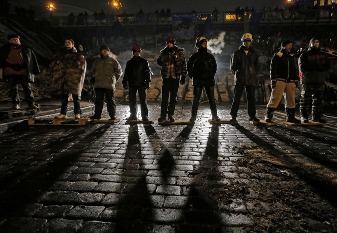 Pro-European Union activists guard barricades near the Independence Square in Kiev, Ukraine, early Friday, Dec. 13, 2013. Ukraine was thrown into crisis last month when President Viktor Yanukovych suddenly backed away from a long-awaited political and economic agreement with the European Union, deciding to focus instead on restoring trade ties with Russia. (AP Photo/Dmitry Lovetsky)