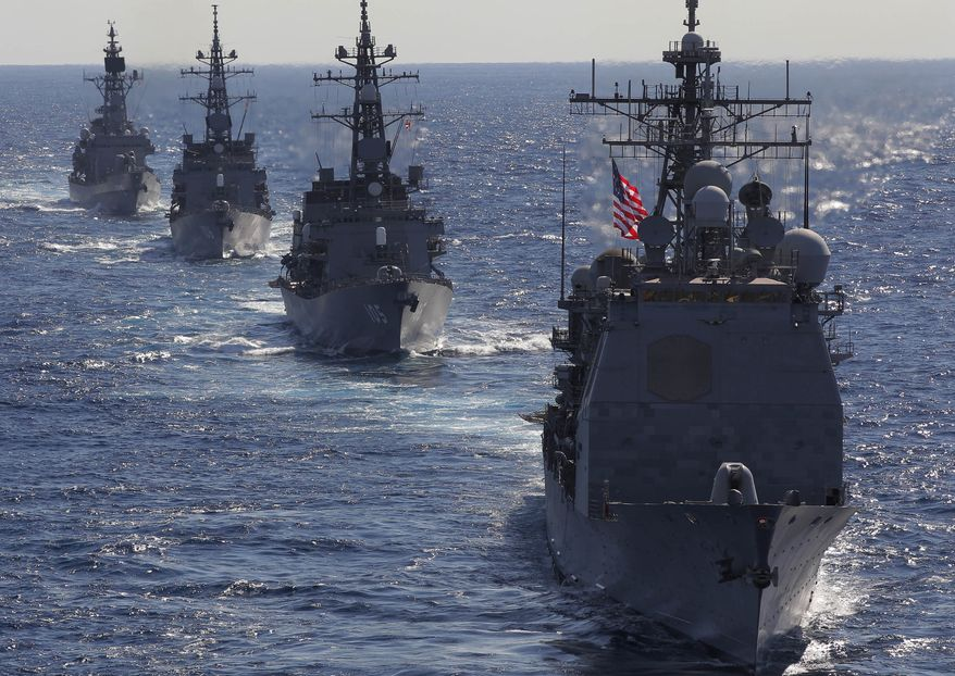 """FILE - In this Dec. 10, 2010 file photo, USS Cowpens (CG63), right, leads Japan Maritime Self Defense Force's vessels during """"Keen Sword"""" U.S.-Japan joint military exercise over the Pacific Ocean, Friday, Dec. 10, 2010. Further U.S.-Japan drills are being held late January through early February in Japan. Even as American and Chinese leaders talked up the need for closer ties in two high-profile visits this month, the U.S. and its Asian allies are quietly boosting their defenses. (AP Photo/Itsuo Inouye, File)"""
