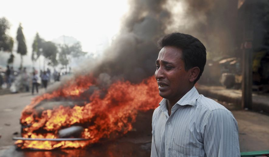 A Bangladeshi man cries after his vehicle was set on fire by Islamist party Jamaat-e-Islami activists following the execution of their party leader Abdul Quader Mollah in Dhaka, Bangladesh, Friday, Dec. 13, 2013. The execution of the opposition leader in Bangladesh sparked violent protests Friday as activists torched homes and businesses belonging to government supporters, leaving at least three people dead, in a fresh wave of bloodshed ahead of elections next month. (AP Photo/Suvra Kanti Das)