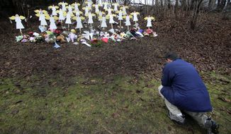 FILE - In this Dec. 18, 2012 file photo, Robert Soltis, of Newtown, Conn., pauses after making the sign of the cross at a memorial to Sandy Hook Elementary School shooting victims in Newtown. Adam Lanza walked into the school on Dec. 14, 2012, and opened fire, killing 26 people, including 20 children, before killing himself. (AP Photo/Charles Krupa, File)