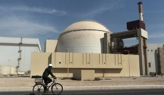 FILE - In this Oct. 26, 2010 file photo, a worker rides a bicycle in front of the reactor building of the Bushehr nuclear power plant, just outside the southern city of Bushehr, Iran. Assassinations, cyber-attacks and possible military strikes: As nuclear negotiations with Iran enter a crucial stage, Tehran is voicing fears that tougher oversight of its activities will increase the risks of an attack on its atomic facilities and the scientists working on them. (AP Photo/Mehr News Agency, Majid Asgaripour, File)