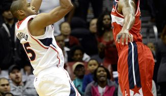 Atlanta Hawks center Al Horford, left, hits a jumper at the buzzer in overtime to score over Washington Wizards' Trevor Booker and win an NBA basketball game on Friday, Dec. 13, 2013, in Atlanta. Atlanta won 101-99 in overtime. (AP Photo/David Tulis)