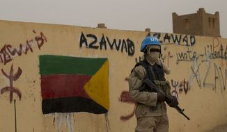 FILE - In this Sunday, July, 28, 2013 file photo, a United Nations peacekeeper stands guard at the entrance to a polling station covered in separatist flags and graffiti supporting the creation of the independent state of Azawad, in Kidal, Mali. A bomb explosion killed several members of the U.N. peacekeeping mission in Mali in the troubled northern city of Kidal, a spokesman for the mission said Saturday, Dec. 14, 2013. (AP Photo/Rebecca Blackwell, File)