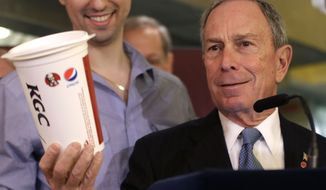 ** FILE ** In this March 12, 2013, file photo, then-New York City Mayor Michael Bloomberg looks at a 64-ounce cup, as  Lucky's Cafe owner Greg Anagnostopoulos, left, stands behind him, during a news conference at the cafe in New York. (AP Photo/Seth Wenig, File)
