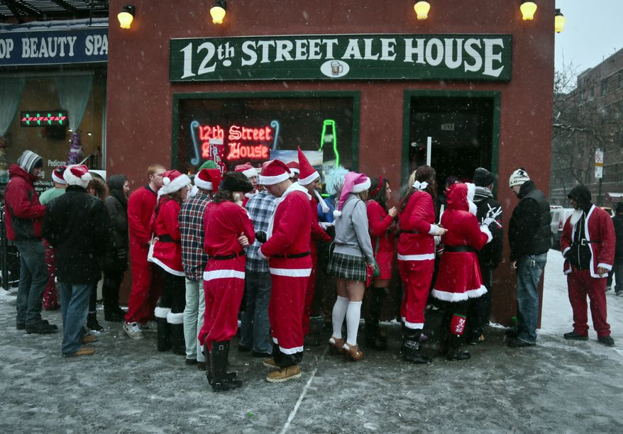 Santacon participants lineup outside a lower eastside bar on Saturday, Dec. 14, 2013, in New York. Thousands of red-suited revelers spread out through the city's bars and snowy streets amid criticism that the event has become too rowdy. (AP Photo/Bebeto Matthews)