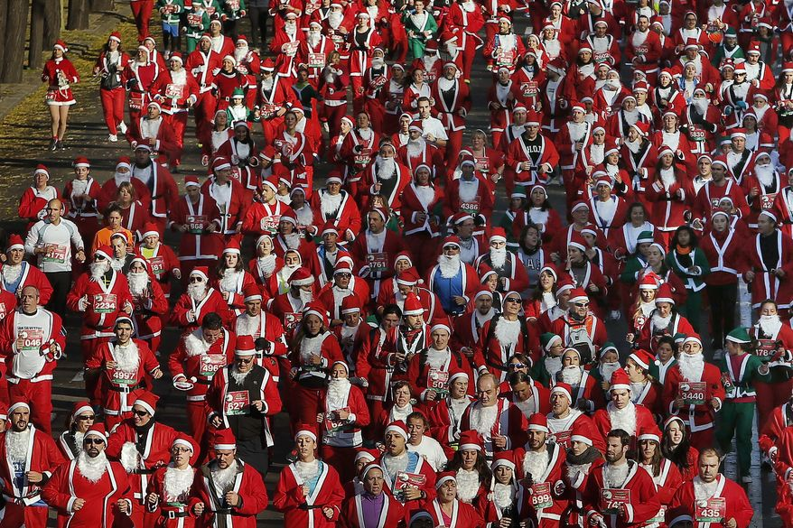 """Revelers dressed as Santa Claus run during a """"mini-marathon"""" in Madrid, Spain, Saturday, Dec. 14, 2013. Around 6,000 people dressed as Santa Claus and his elves have run a """"mini-marathon"""" through the streets of Madrid to promote festive cheer as the country tries to emerge from a two-year recession. While grown-ups dressed in red costumes with wispy white beards, children donned green elf outfits to run the 5.5 kilometer (3.4 miles) course through the city center. The race was organized Saturday by one of Spain's leading department stores and it contributed 1 euro ($1.34) for each entrant to a charity that buys Christmas presents for deprived children around the world. (AP Photo/Andres Kudacki)"""