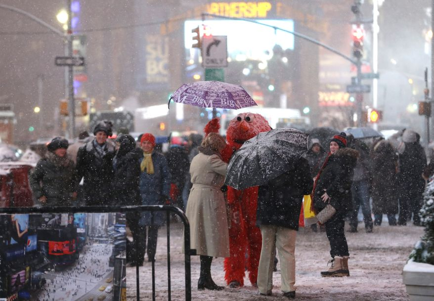 ** FILE ** A person wearing an Elmo outfit holds an umbrella for a woman as she searches for money to give to the character after posing for a photo together at Times Square, Saturday, Dec. 14, 2013, in New York. (AP Photo/Julio Cortez)