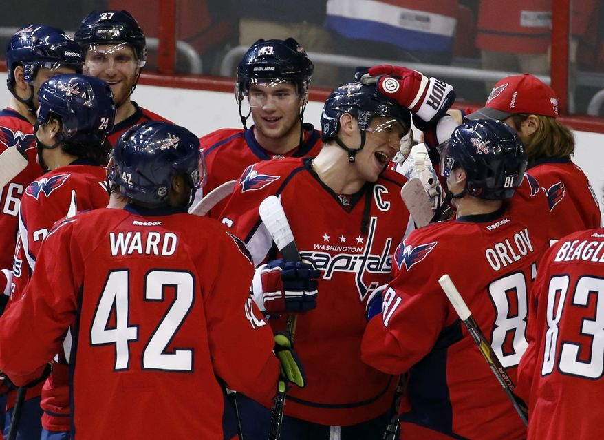 Washington Capitals right wing Alex Ovechkin (8), from Russia, center, celebrates with his teammates including right wing Joel Ward (42) and defenseman Dmitry Orlov (81), from Russia, after an NHL hockey game against the Philadelphia Flyers, Sunday, Dec. 15, 2013, in Washington. The Capitals won 5-4 in a shootout. (AP Photo/Alex Brandon)