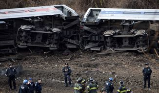 FILE- In this Dec. 1, 2013 file photo, emergency personnel respond to the scene of a Metro-North passenger train derailment in the Bronx borough of New York. Metro-North trains are equipped with an automatic breaking system that might have prevented the crash, but the system was in place to regulate the distance between trains, not to control speeds as trains approached curves, or passed over hills and bridges. Since the crash, the speed limit was lowered on the approach to the curve, plus an alarm will sound and an automatic braking system will engage is a train approaches the bend too fast.  (AP Photo/John Minchillo, File)