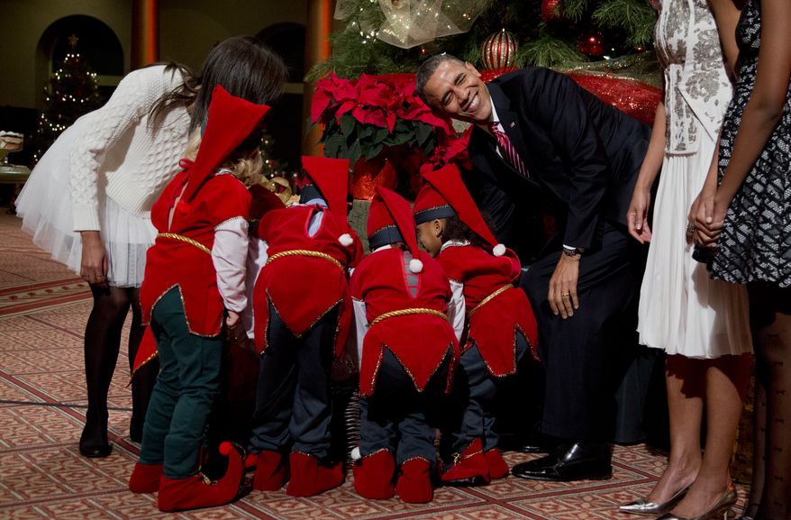 President Barack Obama, laughs as children dressed like elves gathered around a Christmas tree, look at their presents presented to them by the first family at the National Building Museum in Washington, Sunday, Dec. 15, 2013. The first family is attending the taping of the annual 2013 Christmas in Washington, celebrating its 32nd year anniversary. On the left is the president's daughter Malia Obama. (AP Photo/Manuel Balce Ceneta)