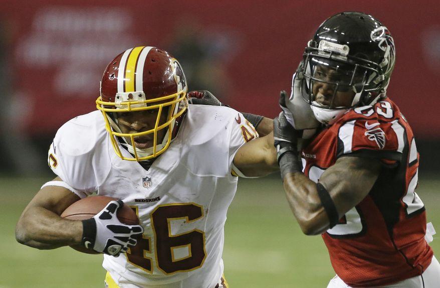 Washington Redskins running back Alfred Morris (46) runs into Atlanta Falcons cornerback Robert Alford (23) during the first half of an NFL football game, Sunday, Dec. 15, 2013, in Atlanta. (AP Photo/John Bazemore)