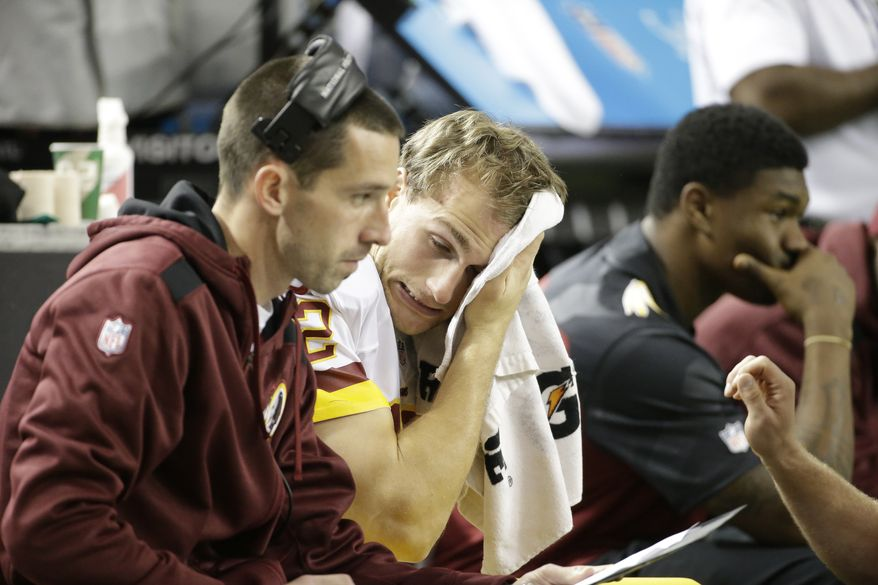 Washington Redskins quarterback Kirk Cousins (12) wipes his face as Washington Redskins offensive coordinator Kyle Shanahan sits on the bench during the second half of an NFL football game against the Atlanta Falcons, Sunday, Dec. 15, 2013, in Atlanta. (AP Photo/David Goldman)