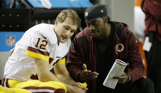 Washington Redskins quarterback Kirk Cousins (12) sits with Washington Redskins quarterback Robert Griffin III, right, during the second half of an NFL football game, Sunday, Dec. 15, 2013, in Atlanta. (AP Photo/David Goldman)