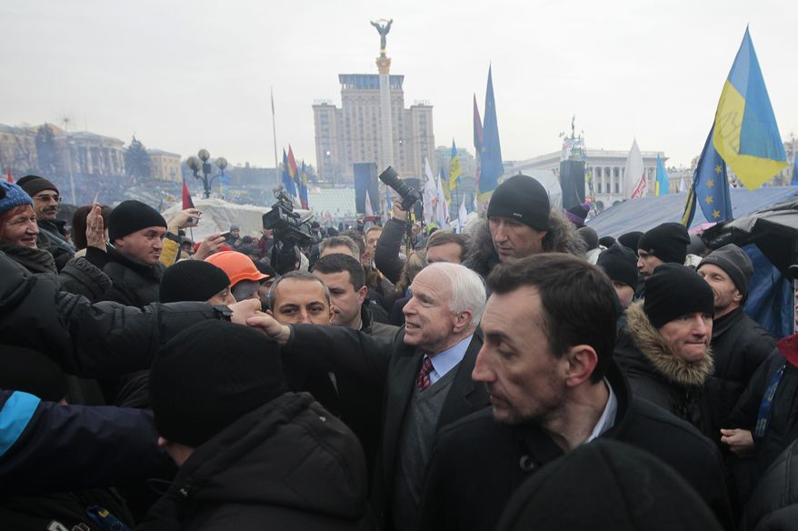 Sen. John McCain (center) greets well-wishers as he arrives to visit a pro-European Union rally in Independence Square in Kiev on Sunday, Dec. 15, 2013. About 200,000 anti-government demonstrators converged on the central square of Ukraine's capital in a dramatic demonstration that the opposition's morale remains strong after nearly four weeks of daily protests. (AP Photo/Sergei Chuzavkov)