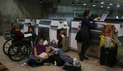 Passengers lie on the floor at the Simon Bolivar International Airport in Maiquetia, Venezuela, near Caracas, on Sunday, Dec. 15, 2013, after Air France Flight 385 to Paris was canceled because of a bomb threat. (AP Photo/Fernando Llano)