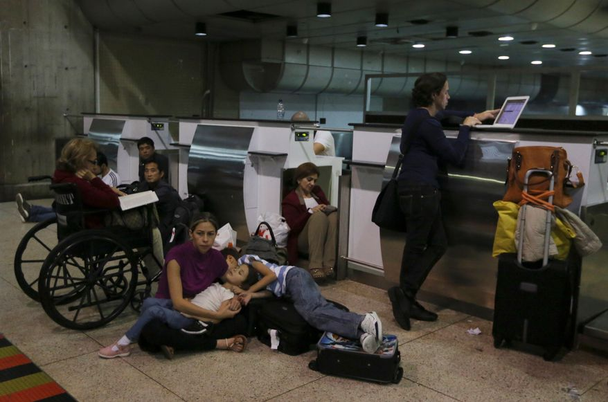 Passengers lie on the floor at the Simon Bolivar International Airport in Maiquetia, Venezuela, near Caracas, on Sunday, Dec. 15, 2013, after Air France Flight 385 to Paris was canceled because of a bomb threat. (AP Photo/Fernando Llano)