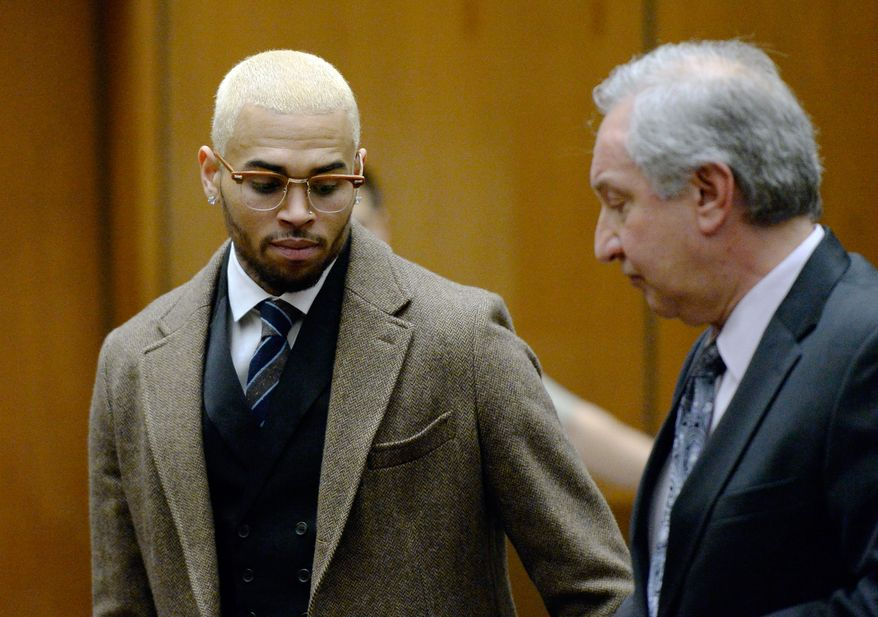 R&B singer Chris Brown, left, appears in court with his attorney Mark Geragos during a probation violation hearing in which his probation was revoked by a Los Angeles Superior judge, Monday, Dec. 16, 2013, in Los Angeles. Superior Court Judge James R. Brandlin revoked Brown's probation after his recent arrest on suspicion of misdemeanor assault in Washington, D.C., but the ruling will not alter the singer's requirements to complete rehab and community labor for his 2009 attack on Rihanna. (AP Photo/Kevork Djansezian, Pool)