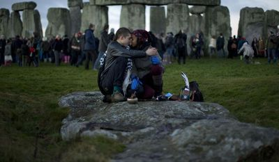 ** FILE ** People embrace by the ancient stone circle of Stonehenge, in southern England on the annual Winter Solstice, in this Friday, Dec. 21, 2012, file photo. British researchers on March 9, 2013, have proposed a new theory for the origins of Stonehenge: It may have started as a giant burial ground around 3,000 B.C. (AP Photo/Matt Dunham, File)