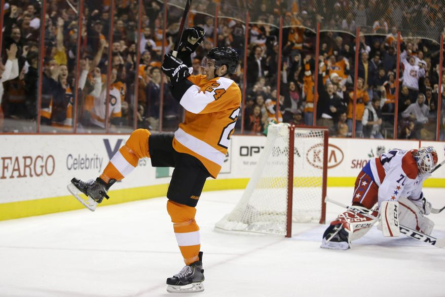 Philadelphia Flyers' Matt Read, left, celebrates after scoring against Washington Capitals' Braden Holtby during the second period of an NHL hockey game, Tuesday, Dec. 17, 2013, in Philadelphia. (AP Photo/Matt Slocum)