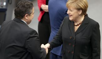 German Chancellor Angela Merkel, right, shakes hands with the chairman of the Social Democrats, designated Vice-Chancellor and Economy Minister, Sigmar Gabriel, at the parliament in Berlin, Germany, Tuesday Dec. 17, 2013, after Merkel was re-elected. Germany's Parliament elected Chancellor Angela Merkel to a third term as the leader of Europe's biggest economic power on Tuesday, nearly three months after an awkward election result forced her to put together a new governing coalition. (AP Photo/dpa, Kay Nietfeld)